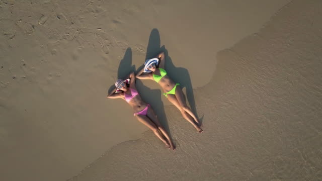Two young woman sunbathing on beach,Aerial view video