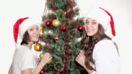 Two young women adorn the Christmas tree video