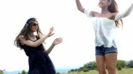Two young women dancing on grass,slow motion video