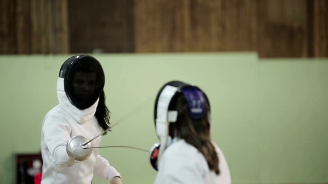 Two young women fencers on a training. Slow motion video