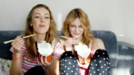 Two young women friends watch together a funny movie. Eat food from wooden chopsticks paper bags video