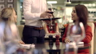MS PAN Two young women in restaurant, waiter serving wine video