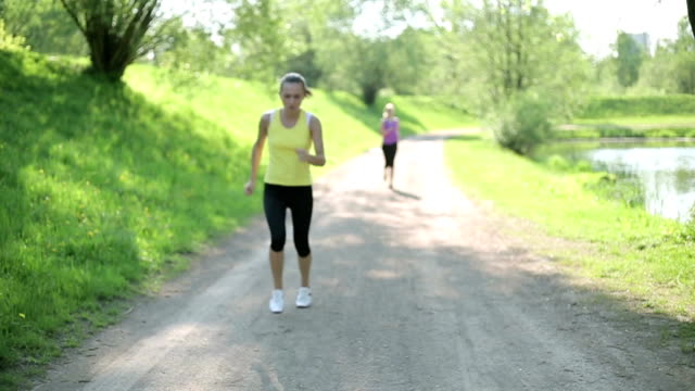 Two young women jogging in the park, slow motion video