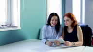 Two young women look to ipad in office or cafe video