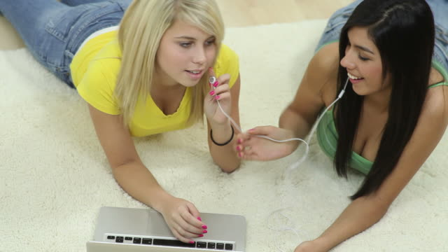 Two young women looking at laptop computer video