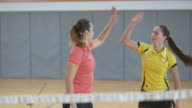 Two young women playing doubles in indoor badminton video