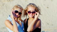 Two young women posing for the camera, smiling. On the beach on a sunny day video