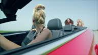Two young women pushing red car along road video