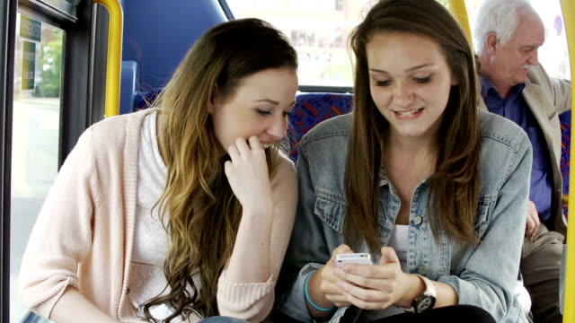 Two Young Women Reading Text Message On Bus video