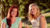 Two young women sharing drinks together in the park video