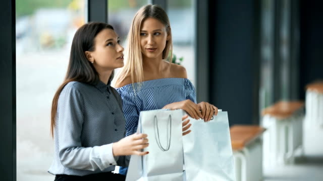 Two young women sharing their new purchases with each other video