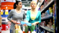 Two young women shopping in supermarket. video