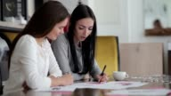 Two young women sitting at a table in the office. video
