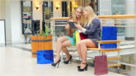 Two young women sitting with shopping bags and used Digital Tablet . Slow motion video
