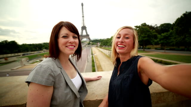Two young women taking selfies in Paris at Eiffel tower-Summer video