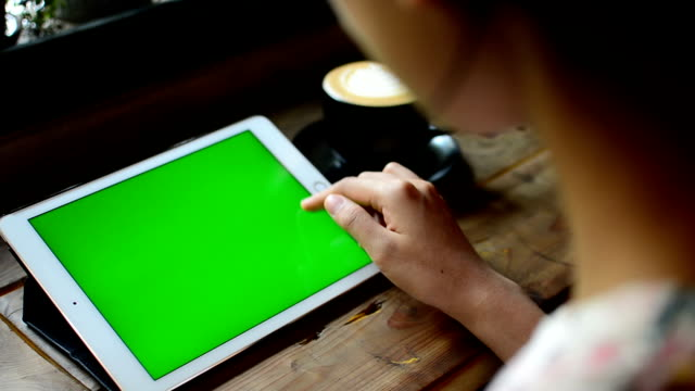 Typing on tablet at coffee shop, with Green screen video