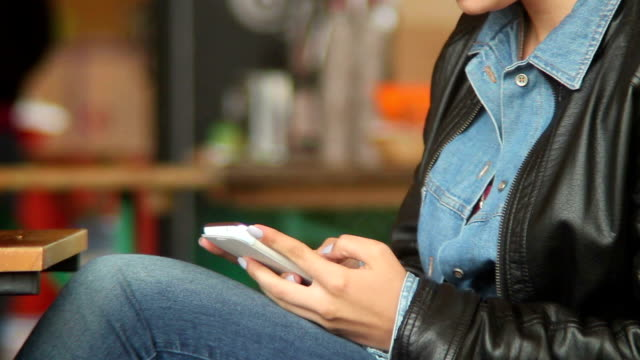 Typing sms message touch phone in public place, female hands video
