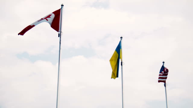 Ukraine and United States and Canadian flags fluttering in wind video