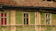 Ultra telephoto shot of an old ruined house with dormers resembling human eyes in the town of Sibiu, Transylvania, Romania video