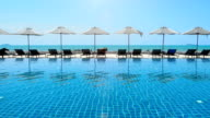 Umbrella and swimming pool in hotel resort with sea beach background. video