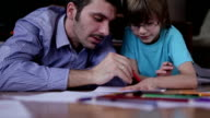 Uncle and nephew drawing and doing homework together video