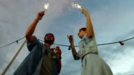 Under view of couple having fun waving with firework candles video