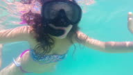 Underwater view of woman with snorkeling mask swiming towards camera and waves video