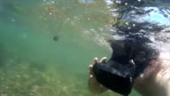 Underwater VR: Man swims through tropical lagoon with virtual reality headset video