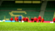 Unfocused background footage of soccer (football) players warming up on the day of the match video
