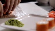 Unfolding Philadelphia sushi rolls on a plate with ginger and wasabi. masters work hand in glove video