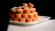 Unfolding sushi rolls philadelphia pyramid on a plate. masters work hand in glove video