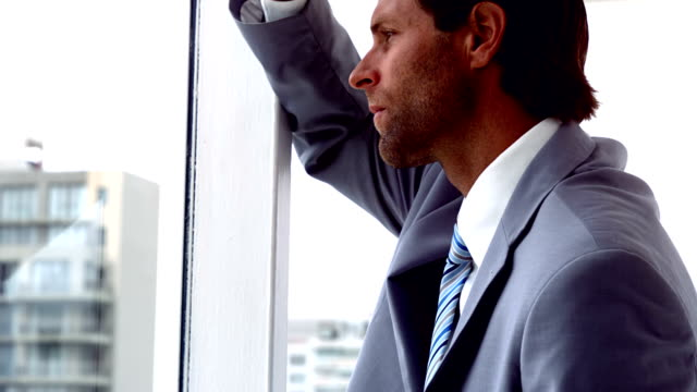 Unhappy businessman looking out window video