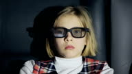 Unhappy child in 3D glasses watching a movie at cinema video