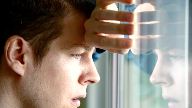 Unhappy man looking out of window video