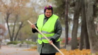 Unhappy overweight woman sweeping city park in autumn, hard-working person video