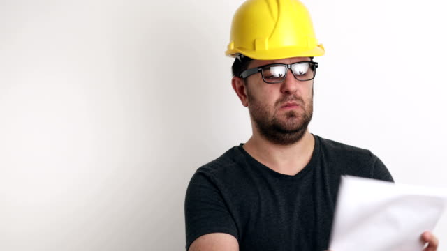 Unhappy portrait of construction worker on white background video