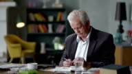 Unhappy sad and troubled elderly man incredulously looks at a pill video