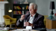 Unhappy sad and troubled elderly man incredulously looks at a pill and take it video