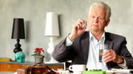 Unhappy sad and troubled elderly man looks at a pill and take it video