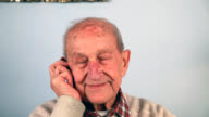 Unhappy senior man talking on the telephone,shaking his head video
