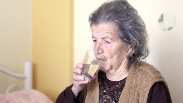 Unhealthy old woman get pills, drink water video