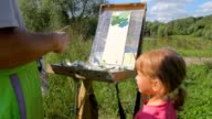 Unidentified man teaching little girl to painting video