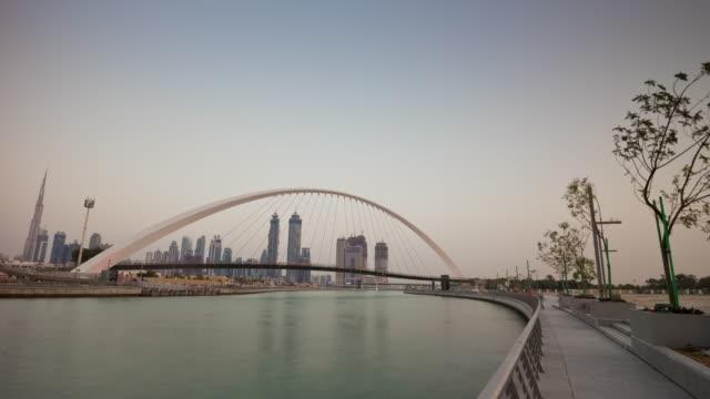 united arab emirates dubai city water canal sunset twilight crossing bridge panorama 4k time lapse uae video