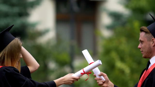 University graduates playing fight with diplomas, competition for employment video