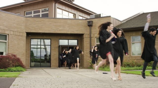 University graduates rushing out of building in excitement video