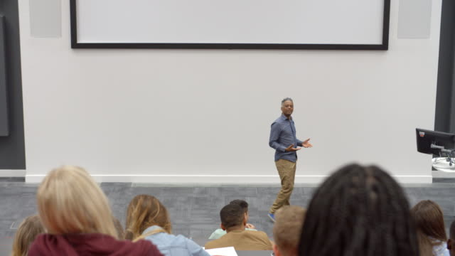 University lecture in lecture theatre, back row student POV video
