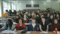 University students in lecture hall raising hands video