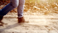 Unknown person walking along the dusty road. Foot close up video