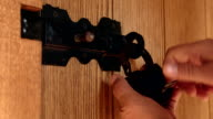 Unlocking padlock on wooden plank door with black sliding bolt video