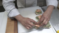 Unrecognisable chef preparing appetisers with smoked salmon and vegetables on a toast video